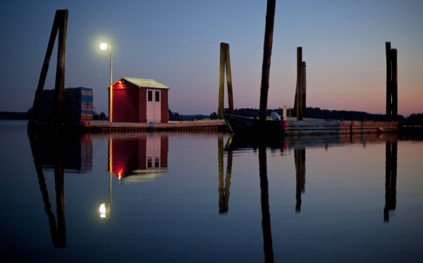 A light shines above a fishermen's shed on a serene evening on Harraseeket River in Freeport.