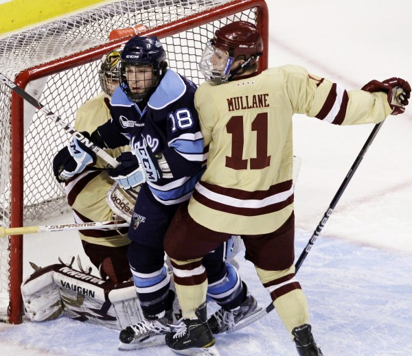 Maine's Jon Swavely (18) is sandwiched between Boston College goaltender Parker Milner, left, and Pat Mullane (11) in the first period of the Hockey East final in Boston, Saturday, March 17, 2012.