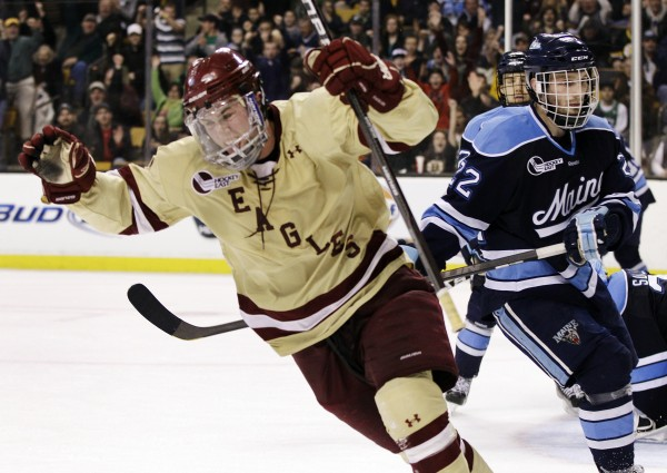 Boston College's Pat Mullane, left, celebrates his goal as Maine's Stu Higgins (22) looks on in the second period of the Hockey East final in Boston, Saturday, March 17, 2012. BC won 4-1.