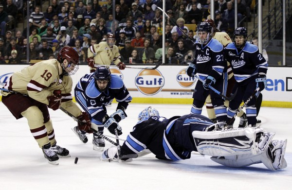 Boston College's Chris Kreider (19) tries to control the puck as Maine goaltender Dan Sullivan dives to protect the net along with teammate Jon Swavely (18) in the second period of the Hockey East final in Boston, Saturday, March 17, 2012.