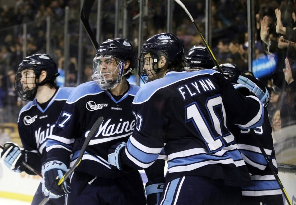 Maine's Matt Mangene (57), Brian Flynn (10) and teammates celebrate an empty-net goal by Joey Diamond against Boston University in the third period of an NCAA college Hockey East semifinal game in Boston, Friday, March 16, 2012. Maine won 5-3.