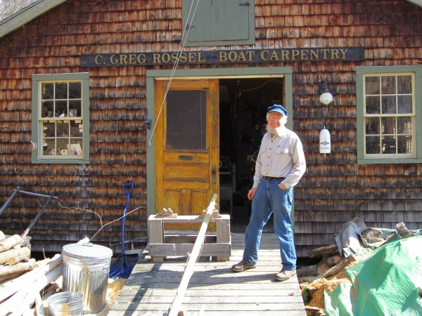 Greg Rossel stands outside his home boat building workshop.