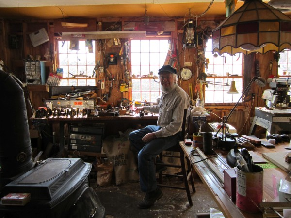 Greg Rossel sits at his workbench inside his boat building workshop.