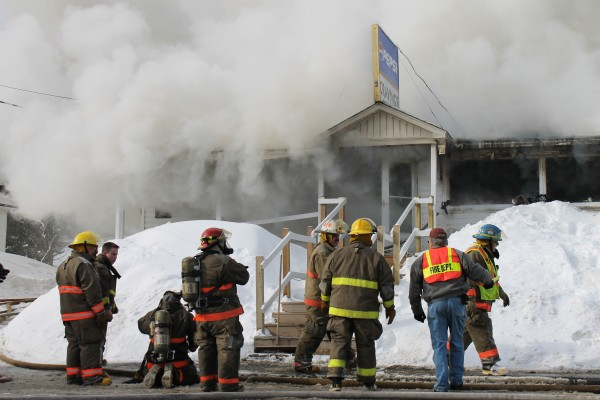Firefighters from multiple communities work Thursday morning to extinguish a blaze at Cravings restaurant in Grand Isle.