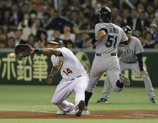 Seattle Mariners' Ichiro Suzuki (51) reaches first past Oakland Athletics first baseman Brandon Allen after hitting a single in the sixth inning of their American League season opening MLB baseball game at Tokyo Dome in Tokyo, Wednesday, March 28, 2012.