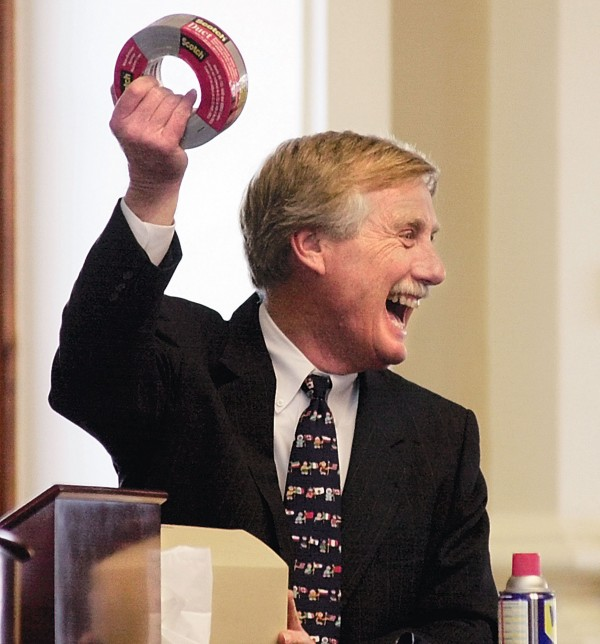 Gov. Angus King holds up a roll of tape he received from Secretary of State Dan Gwadosky along with a can of  WD-40. The gifts are intended for use during the cross-country road trip King has planned.