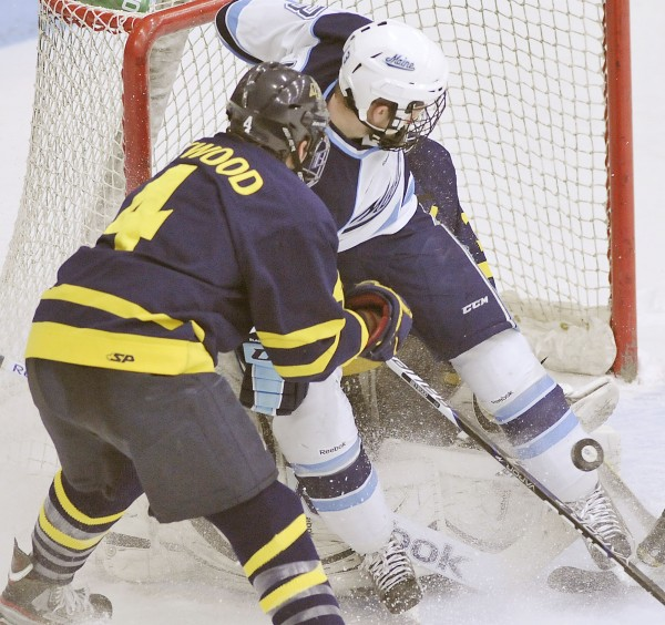 Maine winger Spencer Abbott tries to force the puck past Merrimack goalie Joe Cannata with defenseman Jordan Heywood (4) trying to squeeze Abbott out in the second period of their NCAA hockey game in Orono on Friday, March 9, 2012.