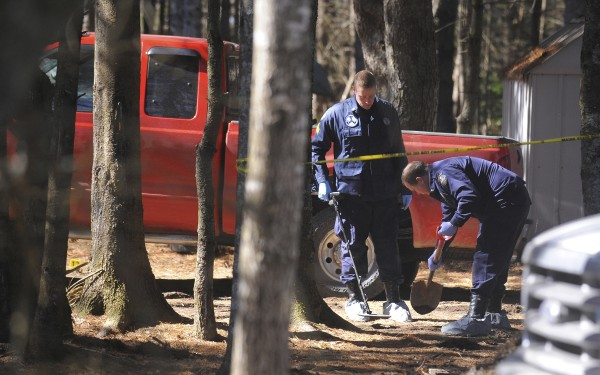 Maine State Police search the grounds for evidence with a metal detector Monday, March 12, 2012, around the Lamoine, Maine home where four people were shot Sunday morning.