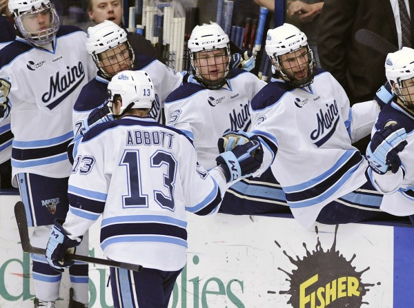 Maine's Spencer Abbott (13) celebrates with teammates after scoring against Merrimack in Maine's 2-1 quarterfinal win on March 11. Abbott suffered a head injury during Maine's Hockey East semifinal win over Boston University on Friday night and his status for Saturday's NCAA Northeast Regional game is still uncertain.