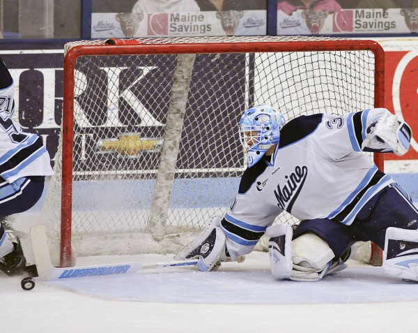 Maine goalie Dan Sullivan (30) dives across the goal to block a loose puck against Merrimack in the first period of a college hockey game on Sunday, March 11, 2012, in Orono.