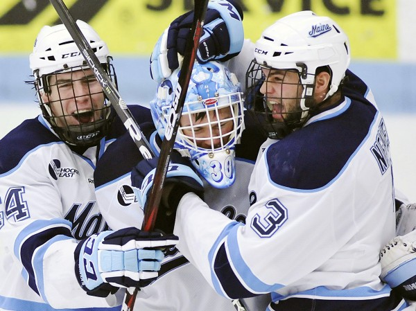 Maine goalie Dan Sullivan (30) celebrates with Ryan Hegarty (44) and Mark Nemec (3) after defeating Merrimack in a college hockey game on Sunday, March 11, 2012, in Orono.