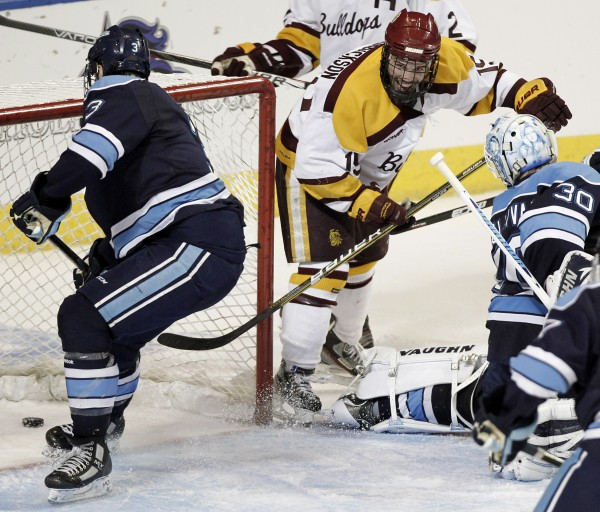 Minnesota-Duluth's Jake Hendrickson stuffs the puck in the goal past Maine defenseman Mark Nemec (3) and goaltender Dan Sullivan during the second period of an NCAA Northeast Regional college hockey game in Worcester, Mass., Saturday, March 24, 2012. Minnesota-Duluth won 5-2.