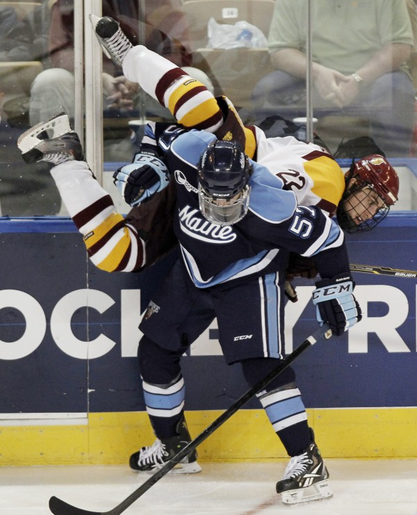 Maine's Matt Mangene (57) upends Minnesota-Duluth's Luke McManus during the third period of Minnesota-Duluth's 5-2 win in an NCAA Northeast Regional college hockey game in Worcester, Mass., Saturday, March 24, 2012.