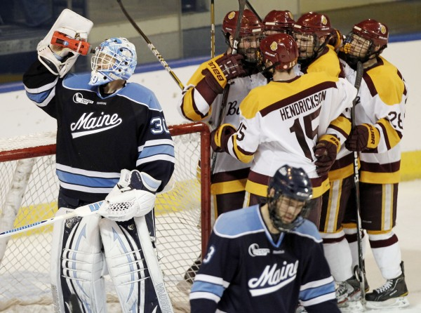 Minnesota-Duluth players, top right, celebrate a goal by teammate Jake Hendrickson (15) as Maine goaltender Dan Sullivan, left, drinks from his water bottle while teammate Mark Nemec, bottom right, skates to the bench during the second period of Minnesota-Duluth's 5-2 win in an NCAA Northeast Regional college hockey game in Worcester, Mass., Saturday, March 24, 2012. Minnesota -Duluth won 5-2.