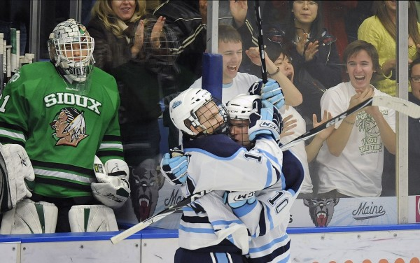 Maine's Spencer Abbott (13) and Brian Flynn (10) celebrate their third period goal in front of the North Dakota bench and goalie Brad Eidsness (31) in Orono in October 2010