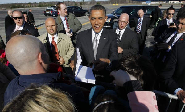 President Barack Obama returns a book after signing it while greeting supporters on the tarmac upon his arrival at Portland International Jetport, Friday, March, 30, 2012 in Portland, Maine. Obama traveled to both Maine and Vermont for campaign fundraisers.