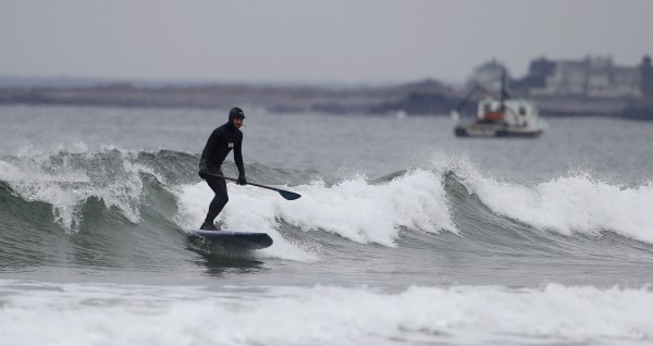 A paddle surfer rides a wave, Thursday, March 29, 2012, at Higgins Beach in Scarborough, Maine, where the ocean temperature was in the 40s. The winter's warm air temperatures are resulting in water temperatures in the Gulf of Maine that are rising well above average, according to scientists.