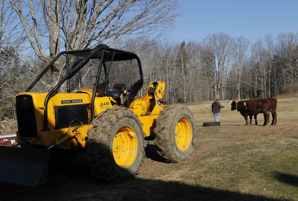 A skidder sits idle as Mike Sproul prepares to lead his team of steer into the woods, Tuesday, March 27, 2012, in Waldoboro, Maine. He uses the animals to twitch logs a couple days a week and uses heavy machinery the other days.
