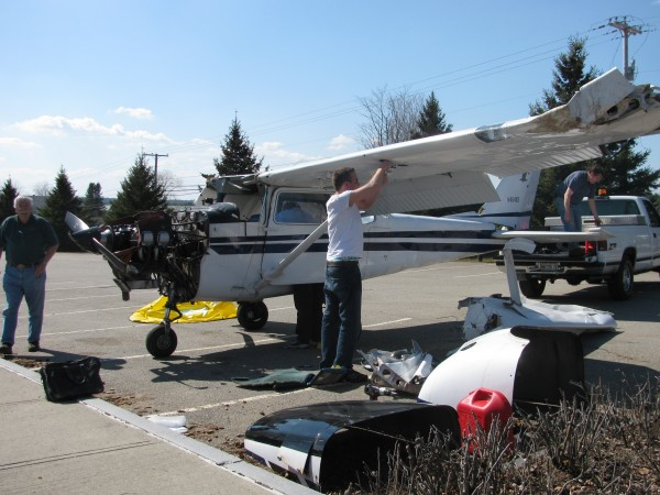 A crew from Columbia Air Service in Trenton worked Wednesday to dismantle a single-engine Cessna that crash-landed on Route 52 the previous night. Neither the pilot nor his 17-year-old flying student were hurt in the accident, but the plane was totaled, according to owner David Vroom of Maine Coastal Flight Center Inc.