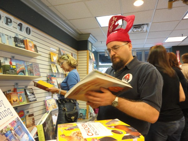 Chris Hourcle dons the red lobster hat and sticker prevalent among participants in Portland's first Cash Mob on Thursday, March 22, 2012. During the event, which was organized by Local Thunder, nearly 50 &quotmobbers&quot brought $20 each and raided Longfellow Books with business.
