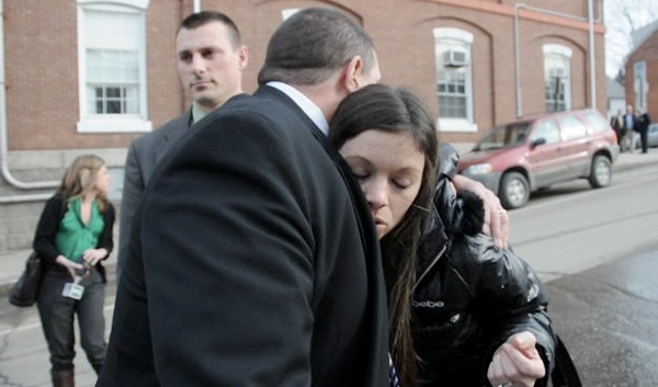 Jerry Perdomo's widow, Tonya Perdomo of Orange City, Florida, hugs Maine State Police Detective Brian Strout, a lead investigator on the Perdomo case, as he and fellow detective Jay Pelletier (behind them) walk her to a vehicle after Daniel Porter's Harnish hearing at Waldo County Superior Court in Belfast on Thursday afternoon, March 8, 2012. Justice Robert Murray denied Porter bail.