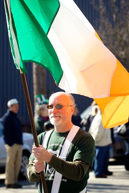 Bob Kearney, vice president of the Irish American Club of Maine, carries the Irish flag in a St. Patrick's Day parade down Commercial Street in Portland Saturday, March 17, 2012.