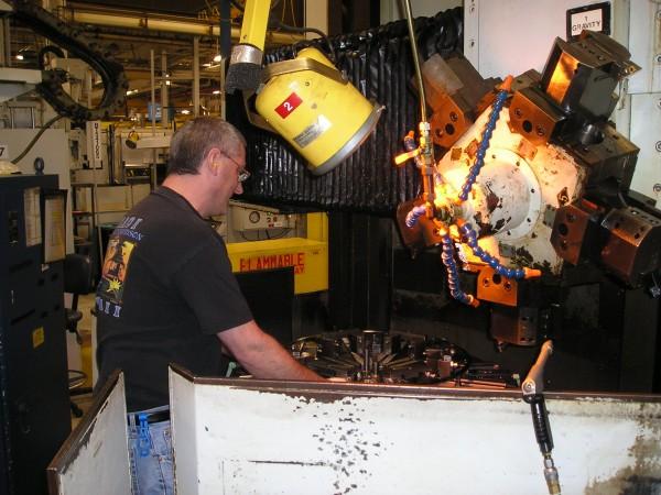 David Veno, a machinist at Pratt & Whitney's plant in North Berwick checks the fixture prior to beginning a vertical turret lathe operation.
