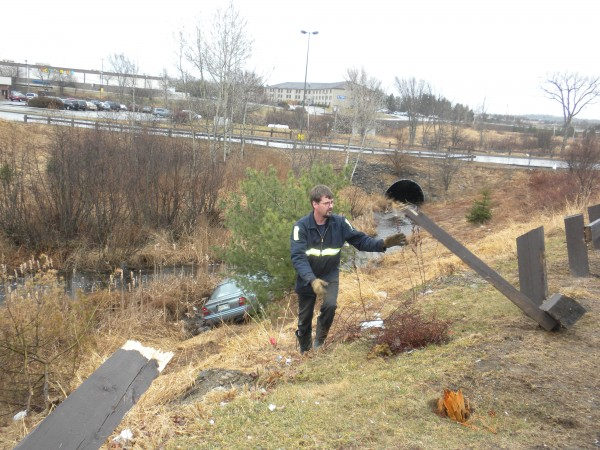 Chris Murray from Union Street Towing throws a piece of wooden fencing to gain access to a crashed car he retrieved on Sunday, March 25, 2012, from the Meadow Brook gully between the Hannaford grocery store parking lot and Arby's near the Bangor Mall.