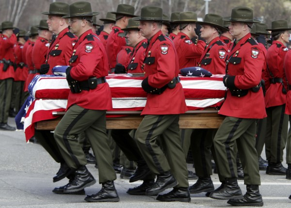 The flag draped casket of Maine Warden Daryl Gordon is escorted into his funeral service, attended by thousands in Augusta, Maine, on Wednesday,  March 30, 2011.