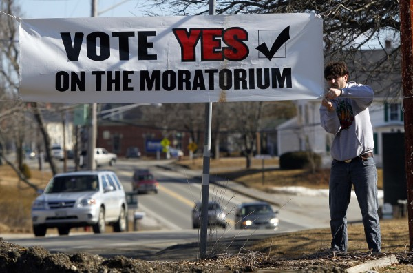 In this Friday, March 9, 2012 photo, Tim Sommer ties up a banner in opposition to a proposed 23-million gallon propane tank in Searsport, Maine.
