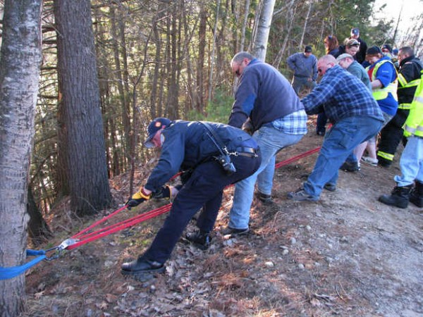 Rumford and Mexico firefighters pull a litter carrying Barbara Cormier, 63, of Canton back to an alley behind Walmart on Tuesday after Cormier tumbled down a vertical embankment through woods to the shore of the Androscoggin River while chasing a wind-blown shopping bag after grocery shopping, police and fire officials said.