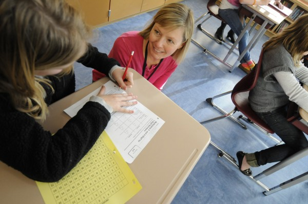 Mary Ellen Seymour (kneeling next to desk), a special education teacher at Brewer Community School, works with a student on math skills during a class that included fifth- and sixth-graders in January 2012.