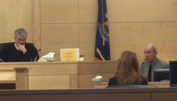 District Court Judge Bruce Jordan listens to testimony from witness Scott Baxter, father of plaintiff Laura Baxter (foreground, facing bench) during a small claims court case at Penobscot Judicial Center on Monday, March 12, 2012.