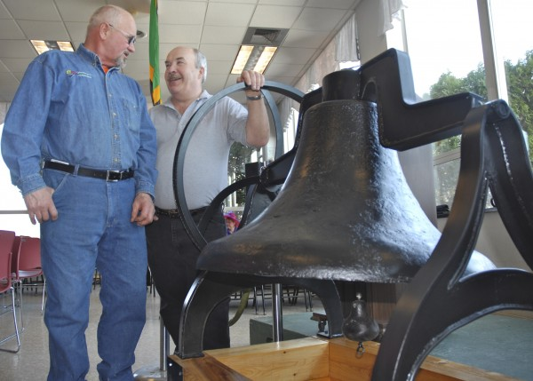 Back when the University of Maine at Fort Kent was the Madawaska Training School, three bells signaled class times, meals and special events. One almost ended up as scrap but was rescued by equipment operator Gilman Babin (left) when he was digging a new storm drain in 1975. After decades as a lawn ornament, the refurbished bell was unveiled on campus Thursday as part of the university's $3  million capital campaign &quotLa Cloche de Fer,&quot or &quotIron Bell.&quot The artifact was brought back to life by local fabricator Tony Voisine (right).