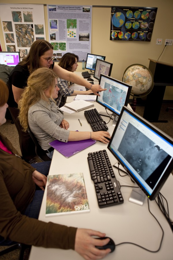 Tora Johnson (standing), the GIS Service Center director at the University of Maine at Machias, instructs a student during a class for a UMM Geographic Information Systems course.