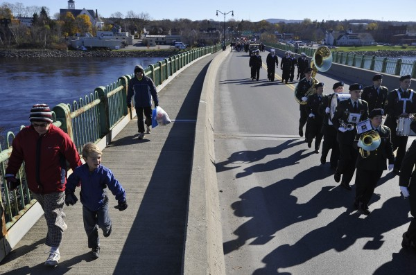 Walking with his grandparents, Jackie Kasper (left) and Gene Kasper (behind them) of Old Town, Aiden Dore of Plymouth, N.H., marched in lock step with members of the Maine Army National guard 195th Army Band over the Joshua Chamberlain Bridge during the Brewer-Bangor Veterans Day parade in November 2010.