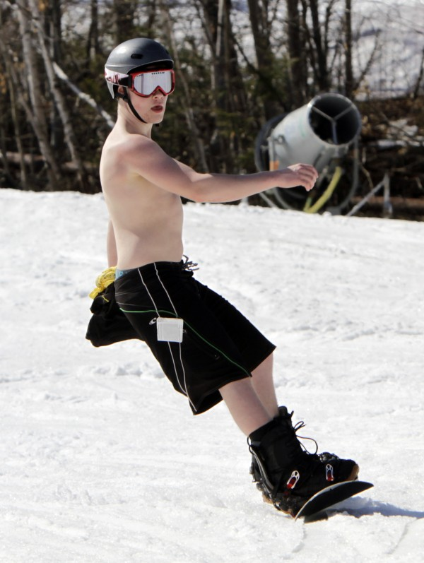 Ben Landry, 15,  from Prince Edward Island, Canada, enjoys the warm sun while snowboarding in unusual weather for this time of year at Sunday River in Newry, Maine, on Wednesday, March 21, 2012.