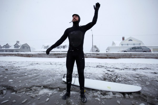 Surfer Daniel Faucette of Santa Barbara, Calif., loosens up before hitting the waves at Gooch's Beach in Kennebunk. Thick neoprene wet suits insulate surfers from the frigid ocean water.