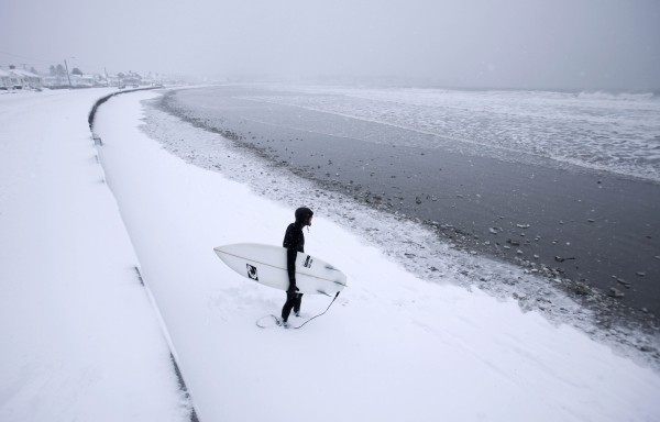 Benny Nadeau of Wells heads out surfing during a snowstorm, Thursday, March 1, 2012, in Kennebunk.