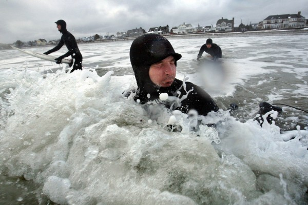 Thomas O'Brien, of Wells, reacts to the cold splash of a 41-degree water as he heads out to surf with friends at Gooch's Beach in Kennebunk on Saturday, March 3, 2012.