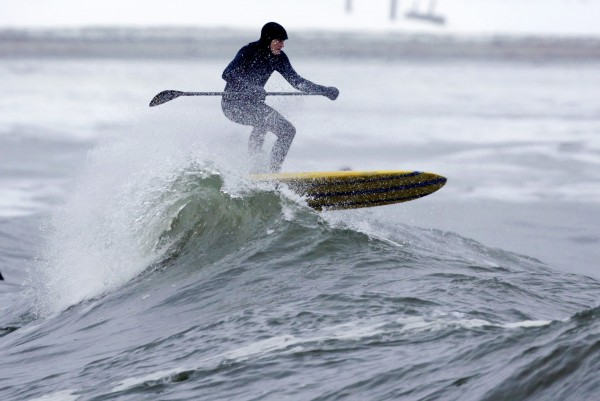 Mark Spalding paddles through a breaking wave at Gooch's Beach in Kennebunk.