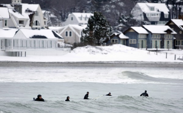Surfers bob like seals while watching for waves at Gooch's Beach in Kennebunk. The season's first big snowfall also brought large swells, attracting surfers from as far away as New Jersey.