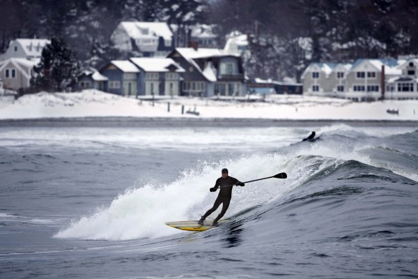 Mark Spalding rides a wave while paddle surfing at Gooch's Beach in Kennebunk. Last week's snowstorm brought large swells with it, giving surfers three good days of riding the waves.