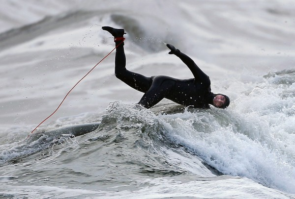 Jamie Gagnon of Wells plunges into the chilly Atlantic Ocean after the wave he was riding started to flatten out on Saturday, March 3, 2012, at Gooch's Beach in Kennebunk.