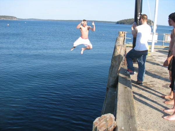 Dakota Stewart of Bar Harbor mugs for the camera as a friend takes a picture of him jumping into the water off the Bar Harbor municipal pier on Thursday, March 22, 2012. Stewart and four other boys, all students at Mount Desert Island High School, took turns jumping off the pier and then scrambling back up a ladder.