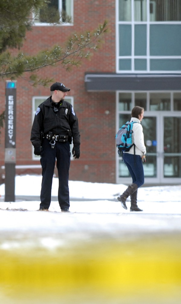 An Orono police officer stands outside Aubert Hall at the Universtiy of Maine after the building was evacuatuted Thursday morning because of a bomb threat.
