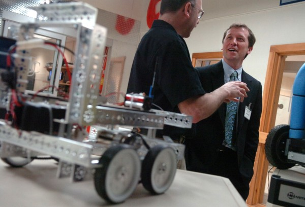 Ron Canarr (left), robotics engineering instructor at United Technologies Center in Bangor, gives Maine Education Commissioner Stephen Bowen a tour of the program's facilities in March 2011.
