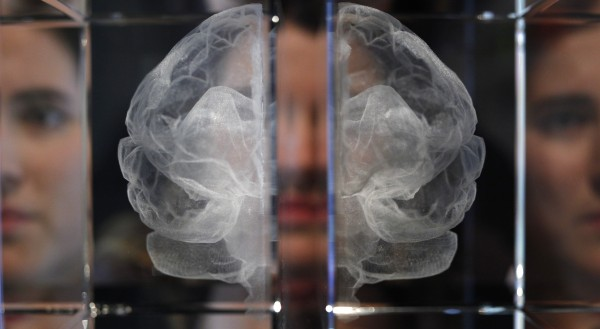 Wellcome Trust employee Zoe Middleton poses for the media by a work entitled 'My Soul' by artist Katherine Dawson, that is a laser etched in lead crystal glass of the artist's own MRI scan, at an exhibition call 'Brains -The Mind as Matter' at the Wellcome Collection in London, Tuesday, March, 27, 2012.