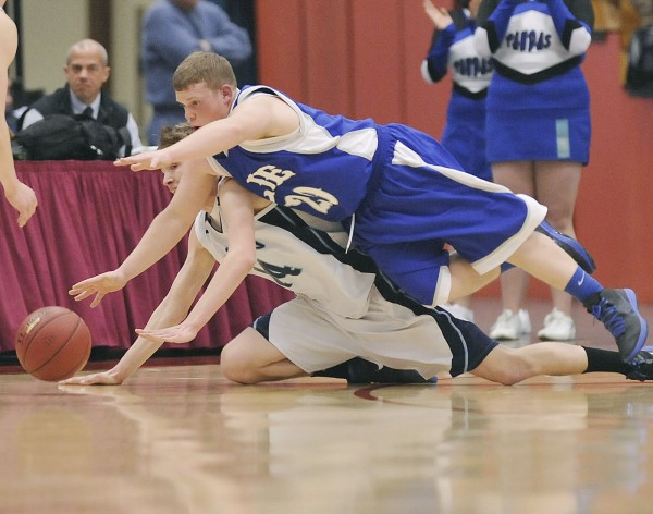 Lee Academy's Dustin Sawtelle (20) and Dirigo center Cody St. Germain (14) dive for a loose ball in the  first half of their  State Class  C championship game  in Augusta, Maine Saturday, March 3, 2012.