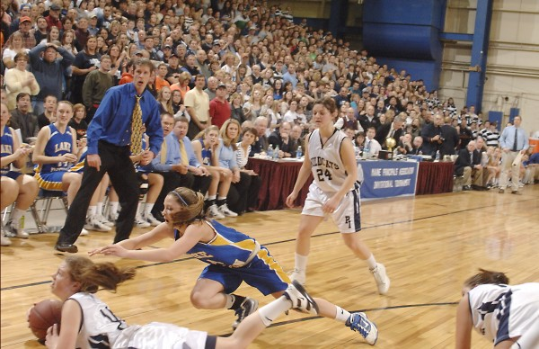 Presque Isle's Chandler Guerette (bottom left) looks at the official as she scrambles for a loose ball with Lake Region player Sydney Hancock (4) in the final seconds of their state Class B championship game at the Bangor Auditorium Friday, March 2, 2012.